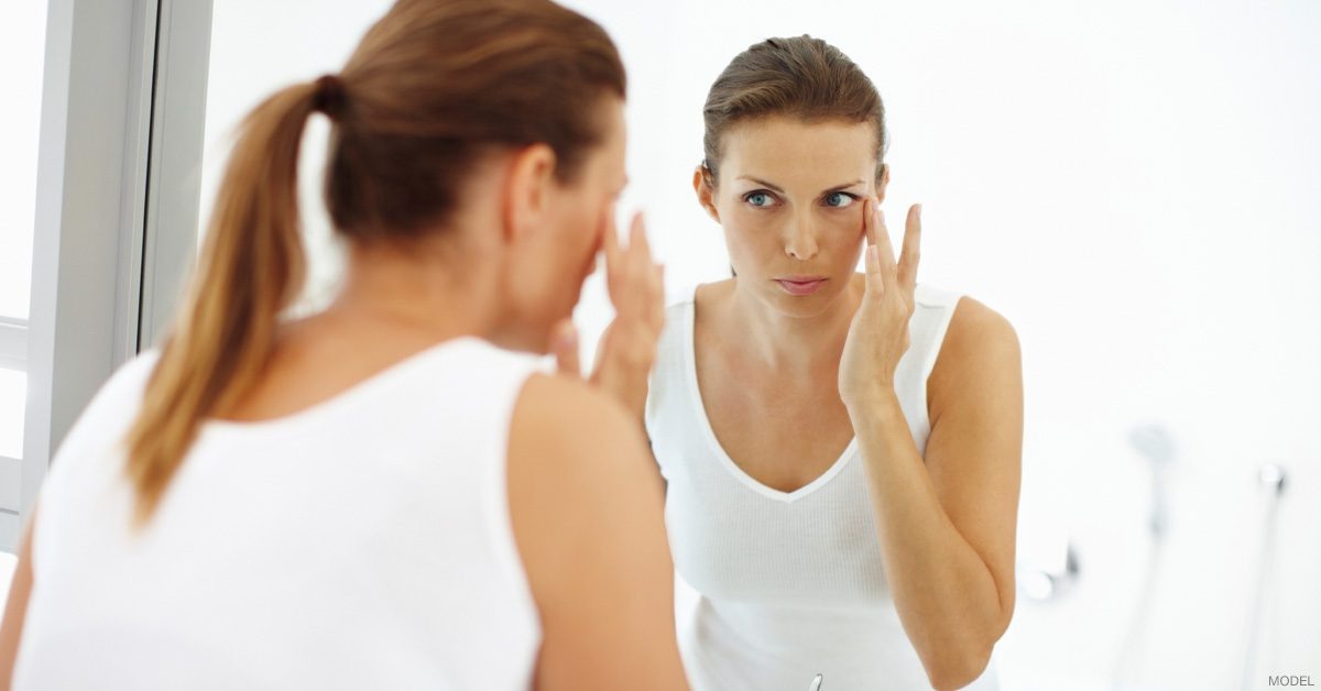 Woman looking in mirror after applying skincare products.